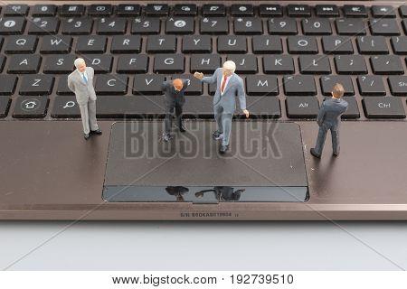Mini Business Men Standing On A Laptop.