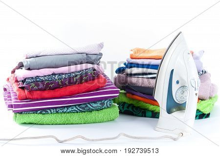 Ironing. Stack of clothing and iron on a white background