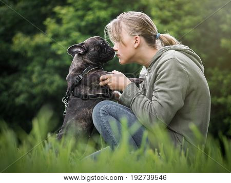 The girl talks to the dog. Nature green grass beautiful