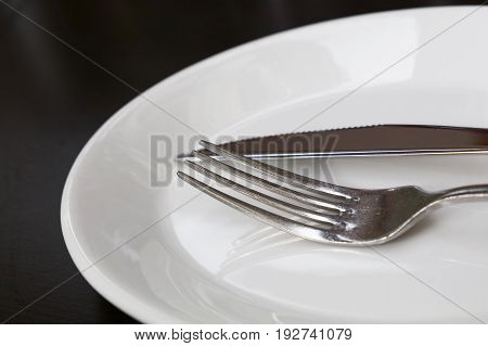 Metal fork and table knife utensils on white porcelain plate on black table close up low angle view