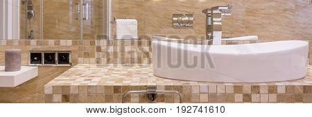 Sand beige bathroom with white sink in panoramic view