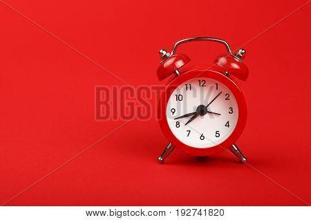 One small metal retro alarm clock with red bells over red paper background close up low angle front view