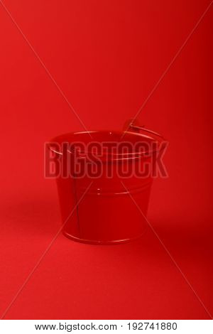 One small red painted metal empty toy bucket over red paper background close up high angle view