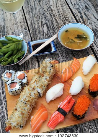 Sushi on wood table. Sushi meal scene featuring a light wood serving tray with nigiri sushi and sushi rolls, miso soup, edamame, soy sauce, chopsticks and wine on a dark wood table