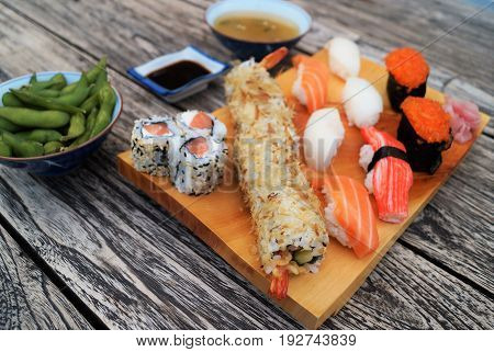 Sushi on wood table. Sushi meal scene featuring a light wood serving tray with nigiri sushi and sushi rolls, miso soup, edamame and soy sauce on a dark rustic wood table