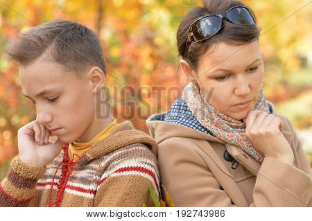 Beautiful sad mother with son in autumn park