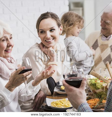Grandparents granddaughter and young married couple sitting beside table during dinner