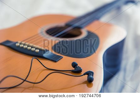music in the bedroom morning concept. guitar with white bed background vintage color tone.