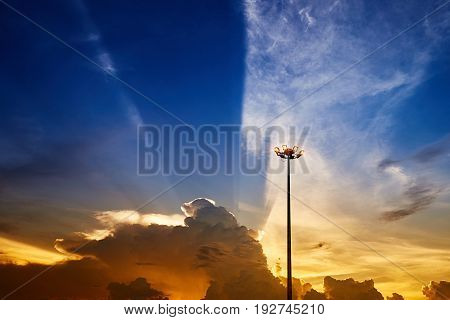Spot-light pole against beautiful sunset sky with clouds light rays and other atmospheric effect