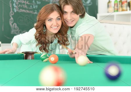 Portrait of a happy young couple playing billiard