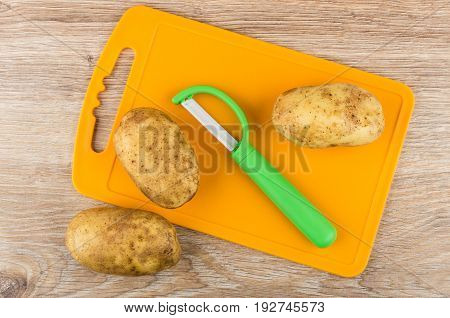 Vegetable Peeler With Ceramic .blade And Potatoes On Cutting Board