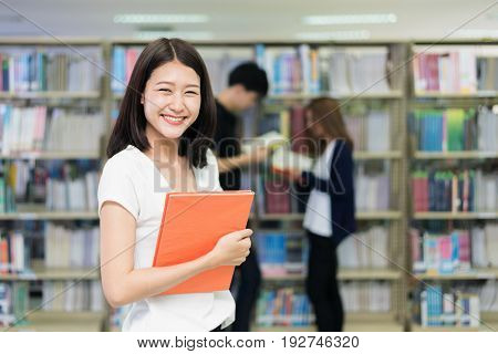 Group of Asian students studying together in library at university. University students.