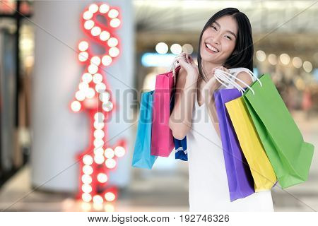 Beautiful Asian woman with shopping bags in shopping mall with sale sign in background. Sale shopping tourism and happy people concept