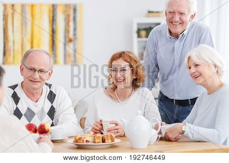 Group of happy seniors meeting at a tea party