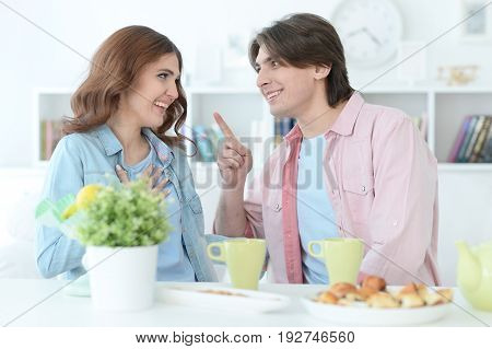 Young couple sitting at table and drinking tea
