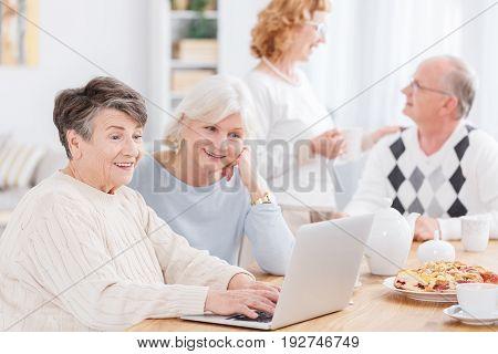 Two senior women using new technology in nursing home
