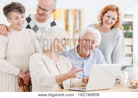 Group of senior friends having video conference with friend