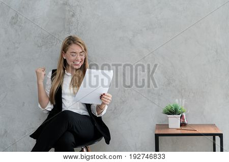 Happy businesswoman with raised in yes gesture hand reading letter at desk in office. Female entrepreneur rejoicing good news from correspondence. Exited woman celebrating achievement win