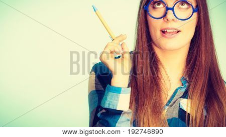 Studying education and fun concept. Nerdy thinking woman in weird big glasses. Studio shot on blue background