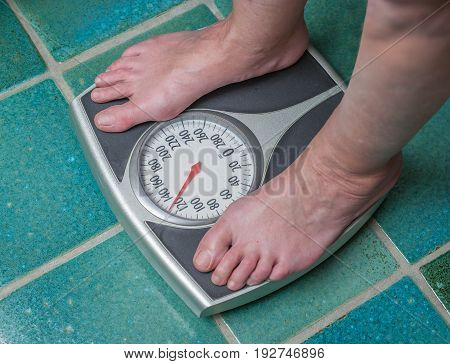 A normal weight person standing on a bathroom scale