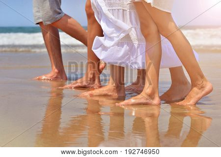 Cropped image of family walking on sandy beach