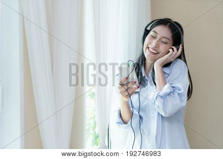 Young Asian woman with headphones listening to music in bedroom at home. Home entertainment and people concept.