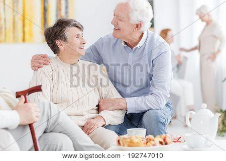 Senior man supporting an older woman in nursing home
