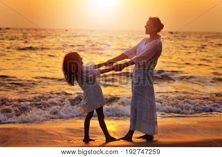 Mother and daughter on sandy beach during beautiful sunset