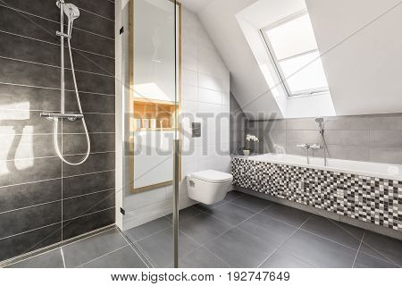 Elegant bright stone bathroom with mosaic bathtub and spacious shower