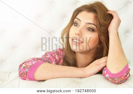 Portrait of beautiful brunette young woman on white couch