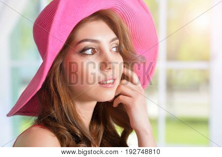 Close up portrait of beautiful brunette young woman in pink hat