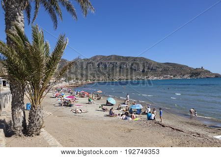 La Azohia Spain - May 14 2017: People relaxing at the beach in town La Azohia. Region of Murcia southern Spain