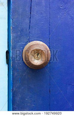 A rusty door knob on blue door.