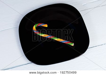 Candycane. Bright striped candy on a black plate and a pale cornflower blue wooden background