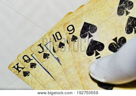 Playing cards with a spades combination in man hand in white glove