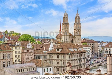 The Grossmunster with town hall in front. It is a Romanesque-style Protestant church in Zurich Switzerland. View from park Lindenhof.
