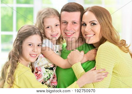 Portrait of a happy family of four standing indoors