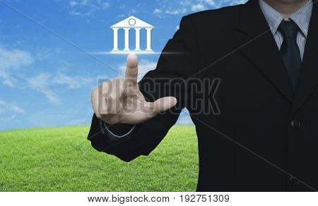 Businessman pressing bank icon over green grass field with blue sky Business banking concept