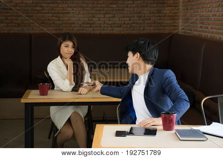 Portrait of attractive businessman holding mobile phone in his hand give it to a beautiful girl. ,Businessman is asking for a girl number in a coffee shop.