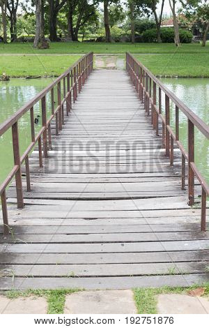 wooden foot bridge over pond in the park with trees.