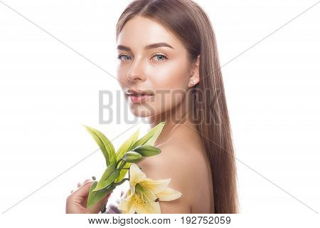 Beautiful young girl with a light natural make-up and perfect skin with flowers in her hand. Beauty face. Picture taken in the studio on a white background.