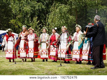 RUSSIAN SOSENSKY JULY 4 2017 White Sunday. Unidentified dancers in folklore ensemble in traditional folk costumes during the Trinity feast in the forest
