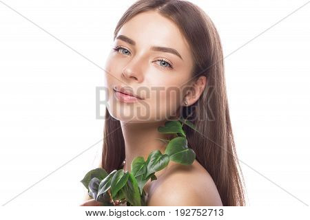 Beautiful young girl with a light natural make-up and perfect skin with Green branch in her hand. Beauty face. Picture taken in the studio on a white background.