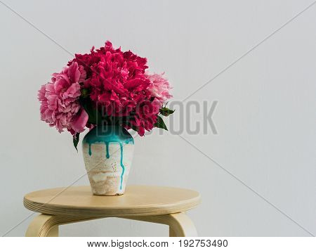 Red peonies in a handmade vase Fresh bouquet of pink and red peonies in white-blue ceramic vase Bright floral bunch on white wall copy space