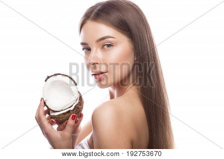 Beautiful young girl with a light natural make-up and perfect skin with coconut in her hand. Beauty face. Picture taken in the studio on a white background.