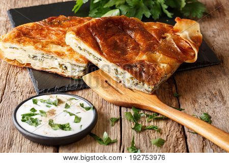 Turkish Burek Stuffed With Spinach And Cheese With Sour Cream Sauce Close-up. Horizontal