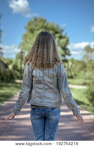 Girl teenager stands withher back with healthy, blond hair