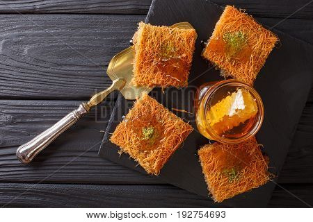 Delicious Middle Eastern Pastries With Pistachios And Fresh Honey Close-up On A Plate. Horizontal To