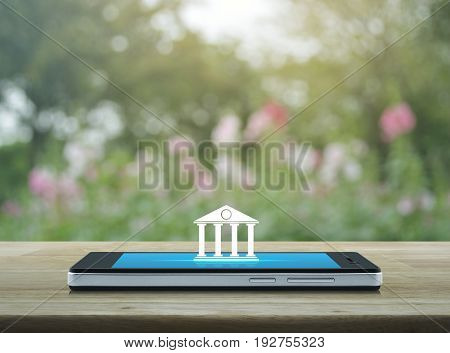Bank icon on modern smart phone screen on wooden table over blur pink flower and tree Mobile banking concept