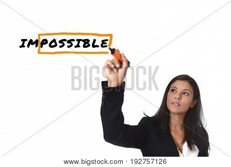 young attractive latin woman in office suit writing with marker on screen or board turning impossible into possible with orange box isolated on white background in business success concept